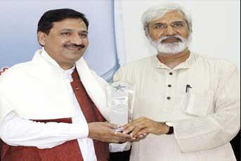 वरिष्ठ पत्रकार राहुल देव से सम्मान लेते संजय द्विवेदी